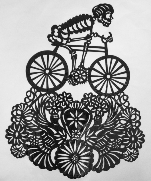 Mexican paper cut artwork of a skeleton on a bike by Catalina Delgado Trunk